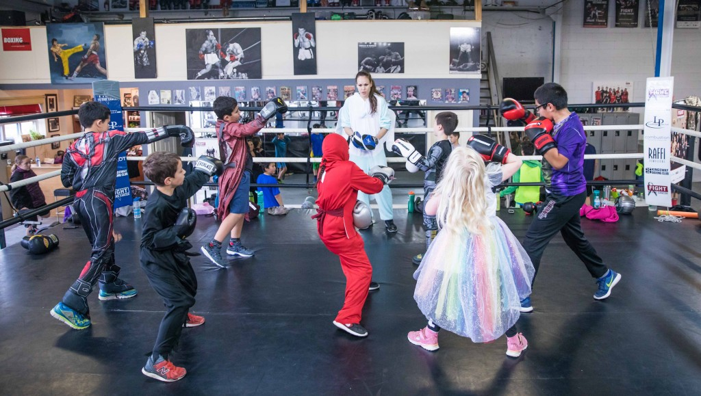The boxing kids ages 7-11 years old eagerly await instruction from coach Jen.